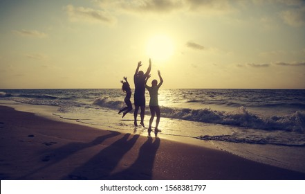 Father with two kids enjoying summer vacation on the beach