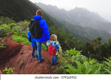 father and two kids hiking climbing in mountains