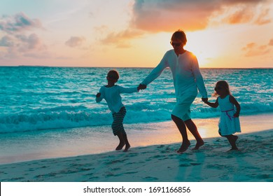 father and two kids play on beach at sunset