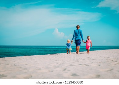 father with two little daughters walking on beach