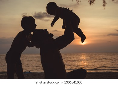 Father and two sons  playing on the beach at the sunset time. People having fun outdoors. Concept of summer vacation and friendly family.