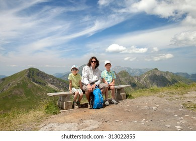 father and two sons are sitting on a bench in the Alps