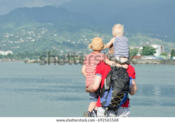 Father with two sons stand on the beach. View from the back