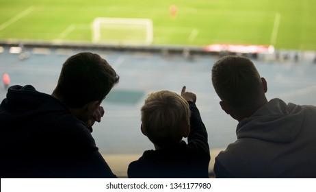 Father and two sons watching football match together, happy weekend, fatherhood