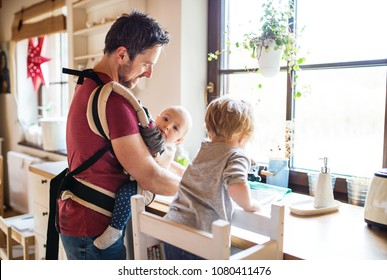 Father and two toddlers washing up the dishes.