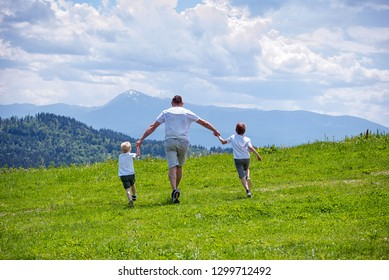 Father and two young sons running on the green field holding hands on background of green forest, mountains and sky with clouds.