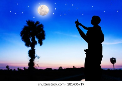 father use hand point the full moon and the star on the sky his son see