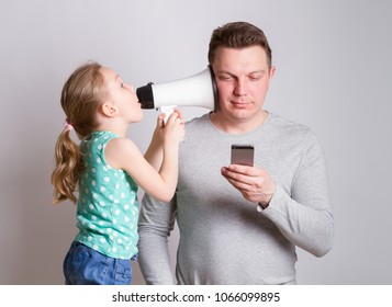 Father using smartphone ignoring his daughter, child tries to attract attention to himself, the parent ignores. in social networks