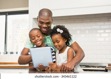 Father using tablet with his children in kitchen at home