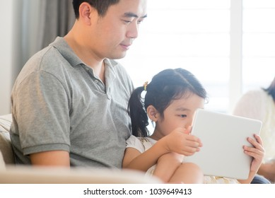 Father using touch screen tablet PC with daughter on sofa. Asian family at home, living lifestyle indoors.