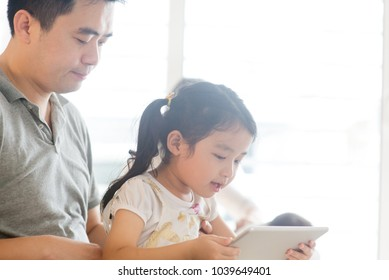 Father using touchscreen tablet PC with child on sofa. Asian family at home, living lifestyle indoors.