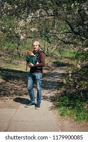 Father walking with baby daughter in the garden, using sling backpack