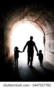 Father walking with his two little siblings children, boy and girl, towards the light at the end of a long dark tunnel