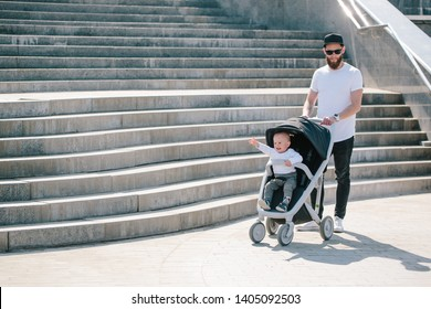 Father walking with a stroller and a baby in the city streets