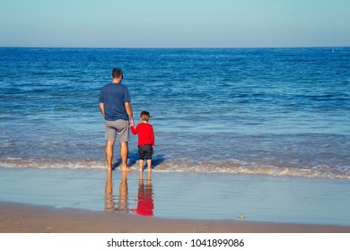 father walking with sun in beach
