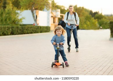 the father walks with the child, ride scooters and Having Fun outdoors