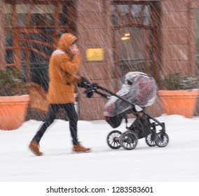 Father walks with the child in the stroller in snowy winter day. Intentional motion blur. Defocused image