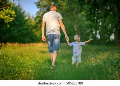 father walks with the little son, holding hands, walk in the evening park