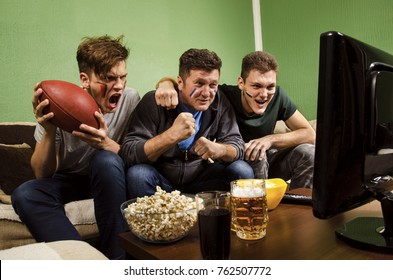 Father watching American football match with his sons and cheering