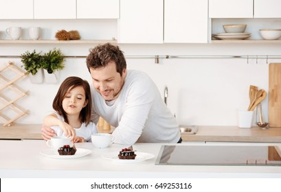 Father watching his daughter treating herself to cake