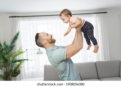A father wit his baby daughter having funny on the living room