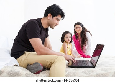 father working on the laptop with mother and daughter in the background, Indian family of three using laptop