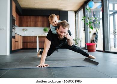Vater arbeitete sich aus und machte einen Arm plank, während sein fröhliches Kleinkind auf dem Nacken reitete. Zu Hause Wohnung.