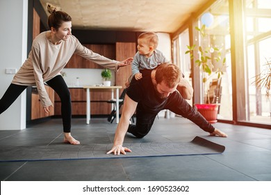 Father working out, doing single arm plank with his jolly infant baby riding on his neck. At home apartment. Amused mom wants to check out the baby