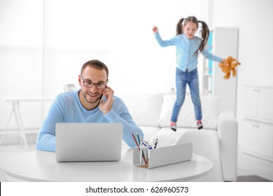 Father working while his daughter having fun at office