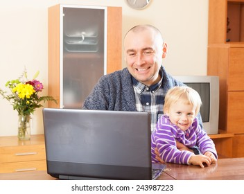 Father works at a computer and holding daughter