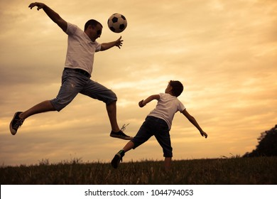 Father and young little son playing in the field  with soccer ball. Concept of sport.
