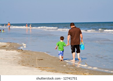 Father with young son walking on the beach in South Carolina.