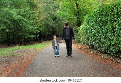 father and young son walking in a park