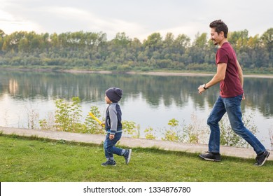 Fatherhood and family concept - Laughing father trying to catch funny son