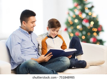fatherhood, family and people concept - happy father and son reading book at home over christmas tree background