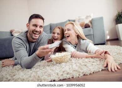 Father,mather and daughter lying on floor,watching TV and eating popcorn.