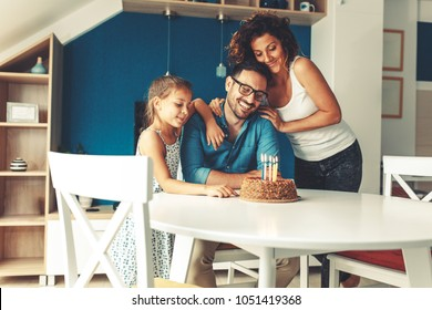 Father's birthday.Wife and daughter surprise father with birthday cake .
