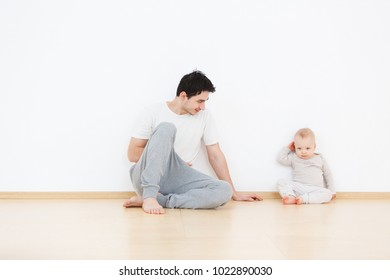 Father's care. Little kid sits next to positive cute young dad talking and playing in cozy home atmosphere. White wall background