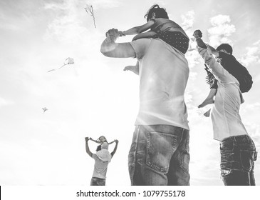 Fathers with children flying with kites and having fun on the beach - Families friends playing with kids on summer weekend - Travel and holidays concept - Focus on center man body