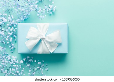 Father's day background, blue background with white flowers and a present