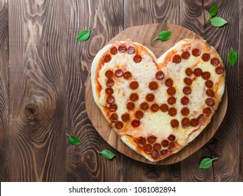 Father's day background with pizza in heart shape and dad word. Pepperoni pizza in heart shape with dad lettering on wooden tabletop. Copy space for text. Father day concept, recipe and idea