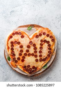 Father's day background with pizza in heart shape and dad word. Pepperoni pizza in heart-shape with dad lettering on gray background.Copy space for text. Father day concept,recipe and idea. Vertical