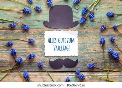 """Father's Day card with cardboard hat and mustache and blue flowers. German greeting """"Alles gute zum Vatertag!"""", which means """"Happy Father's Day""""."""