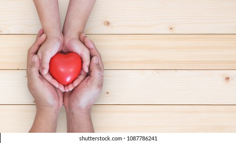 Father's day celebration, I love you dad, parenting concept with daddy and child's hand holding heart young kid's hands supporting red heart, csr charity donation, adoption family health nursing care