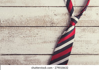Fathers day composition of colorful tie laid on wooden floor backround.