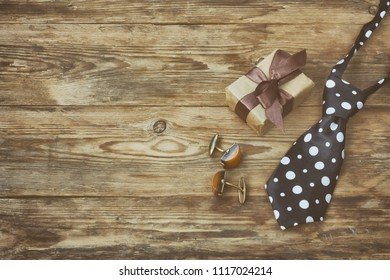 Fathers day composition, gift box, tie and vintage cufflinks on wooden table, retro style