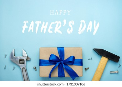 Father's day composition. Gift box wrapped in kraft paper with blue ribbon bow and hand tools on blue background. Happy father's day greeting card. Top view flat lay.