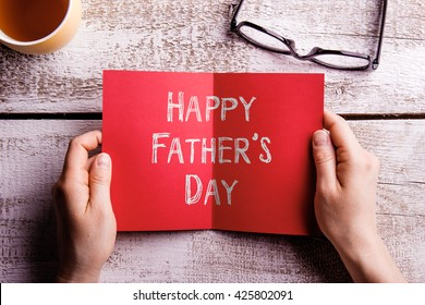 Fathers day composition. Hands of dad holding greeting card. Fathers day. Concept for fathers day celebration. Best father. Child and father concept. Happy fathers day text.