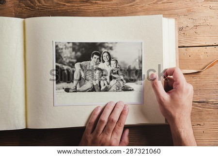 Fathers day composition - photo album with a black and white photo. Studio shot on wooden background.