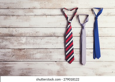 Fathers day composition of three ties hang on wooden wall backround.